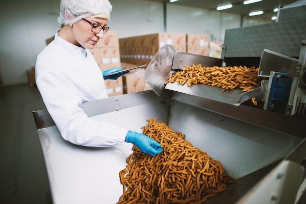 Молодая работница в стерильной одежде берет образец соленых закусок с производственной линии.