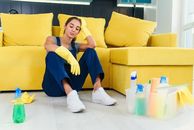 ソファのそばに座って、料理の床を洗った後疲れたクリーニングサービスの若い女性労働者。