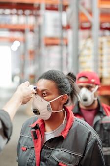 방독면과 작업복을 입은 창고의 젊은 여성 노동자 뒤에 다른 노동자들의 줄과 함께 체온을 측정하고 있다