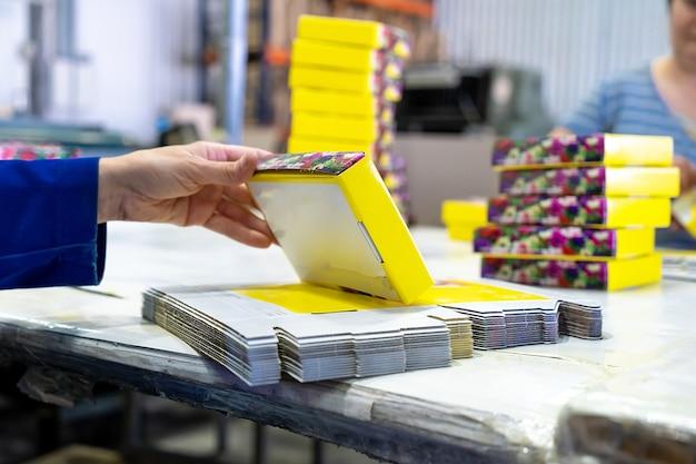 倉庫で出荷するための若い女性労働者の梱包箱。