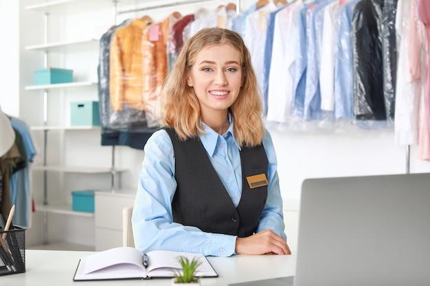 Молодая работница, сидящая на рабочем месте в химчистке