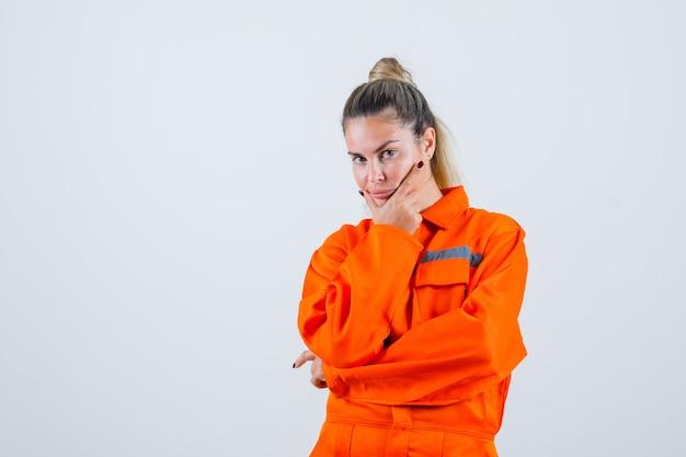 Giovane donna in uniforme da lavoro tenendo la mano sulla sua mascella mentre guarda lontano e guardando pensieroso, vista frontale.