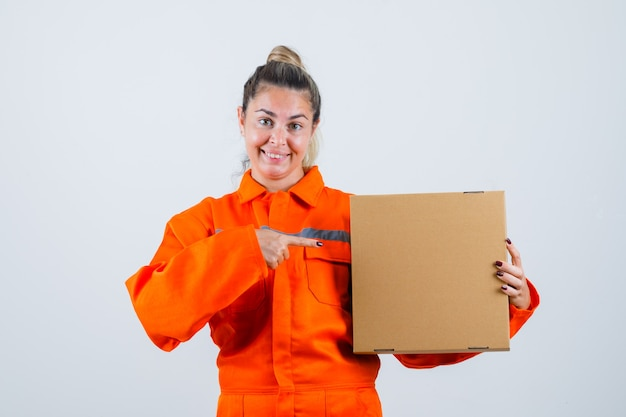 Young female in worker uniform pointing at box and looking glad , front view.