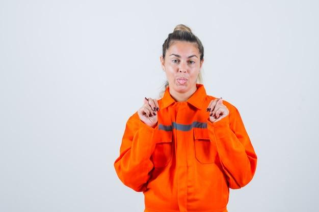 Giovane femmina in uniforme del lavoratore che mostra il gesto del fico, che attacca fuori la lingua e che sembra pazzo, vista frontale.