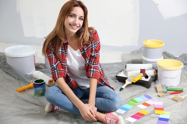 部屋で修理をするツールを持つ若い女性労働者
