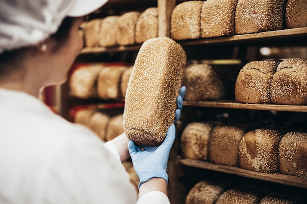 パン屋で働く若い女性労働者。彼女はパンを棚に置きます。