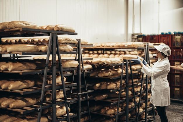 빵집에서 일하는 젊은 여성 노동자. 그녀는 선반에 빵을 놓습니다.