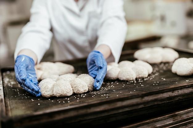 大きなパン屋で働く若い女性労働者。パンの準備。