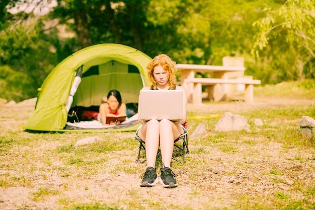 Молодая женщина работает на ноутбуке в сельской местности