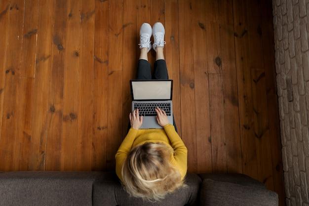 Молодая женщина работает на современном ноутбуке, сидя на полу у себя дома.