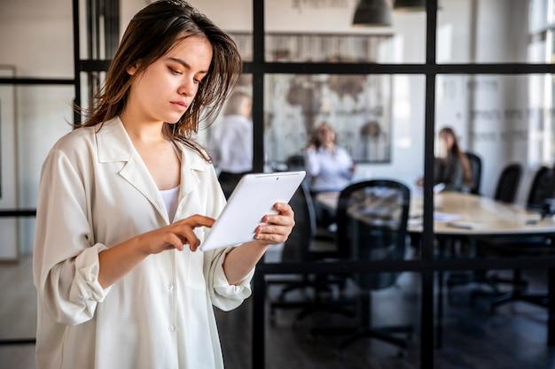 Молодая женщина работает на планшете