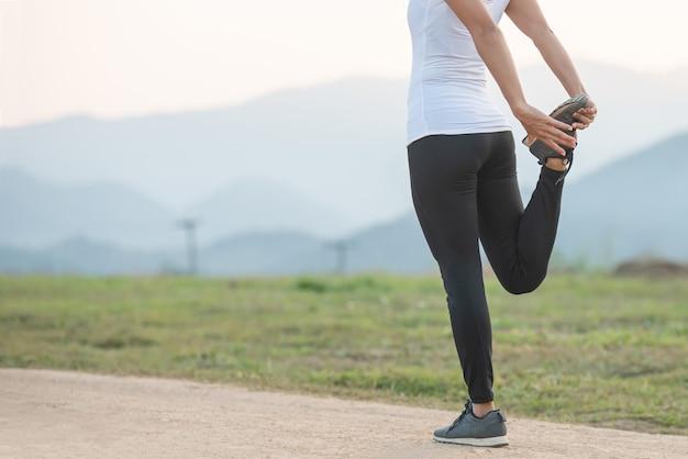 公園でのフィットネストレーニングセッションの前に若い女性のトレーニング。