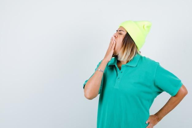 ポロtシャツ、ビーニー、眠そうな顔で腰に手を当てながらあくびをする若い女性。正面図。