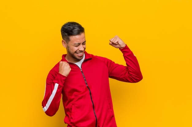 Young filipino fitness man raising fist after a victory, winner concept.