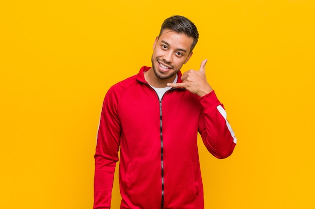 Young filipino fitness man showing a mobile phone call gesture with fingers.