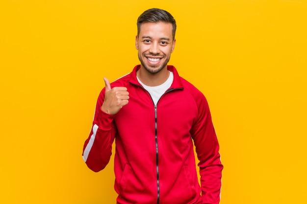 Молодой филиппинский фитнес-мужчина улыбается и поднимает палец вверх