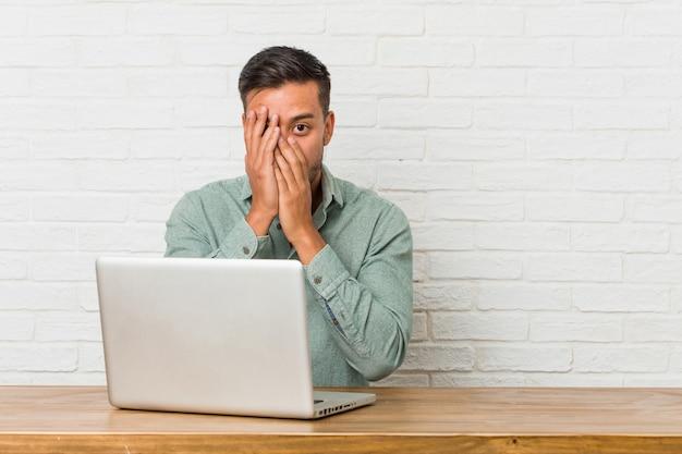 彼のラップトップで働いて座っている若いフィリピン人男性は、おびえ、神経質な指をまばたきします。