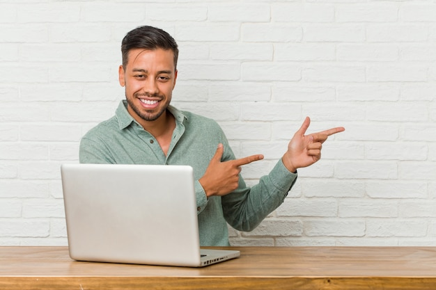 Young filipino man sitting working with his laptop excited pointing with forefingers away