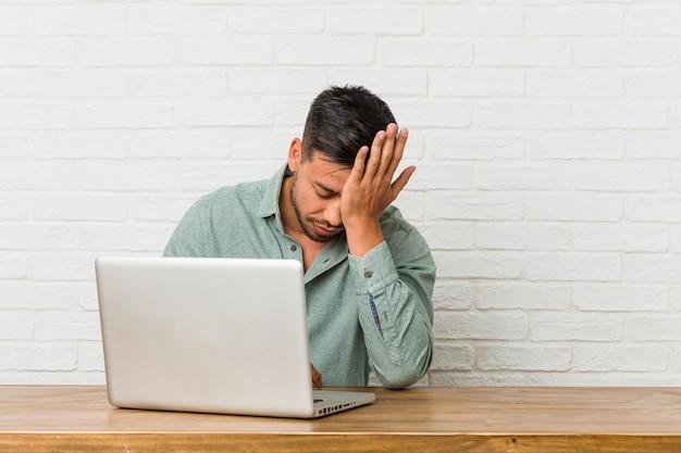 何かを忘れて、手のひらで額を叩き、目を閉じて、ラップトップで作業している若いフィリピン人男性。