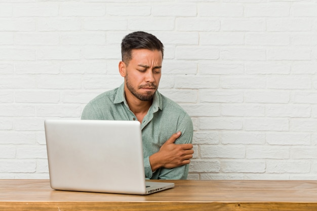 Young filipino man sitting working with his laptop going cold due low temperature or a sickness.