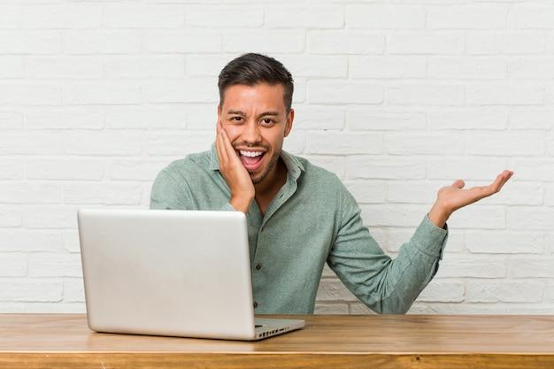 彼のラップトップで作業して座っている若いフィリピン人男性は、手のひらにコピースペースを保持し、頬に手を置いてください。驚きと喜び。