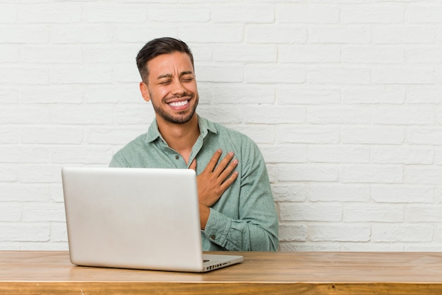 Young filipino man sitting working with his laptop laughing keeping hands on heart, concept of happiness.