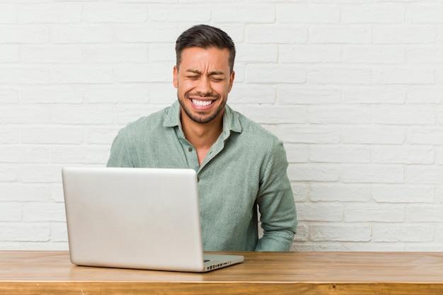 彼のラップトップで働いて座っている若いフィリピン人男は笑って目を閉じて、リラックスして幸せを感じています