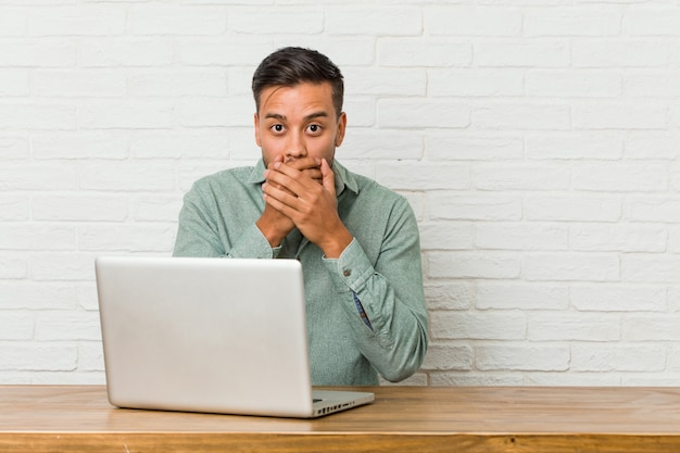 Young filipino man sitting working with his laptop shocked covering mouth with hands.