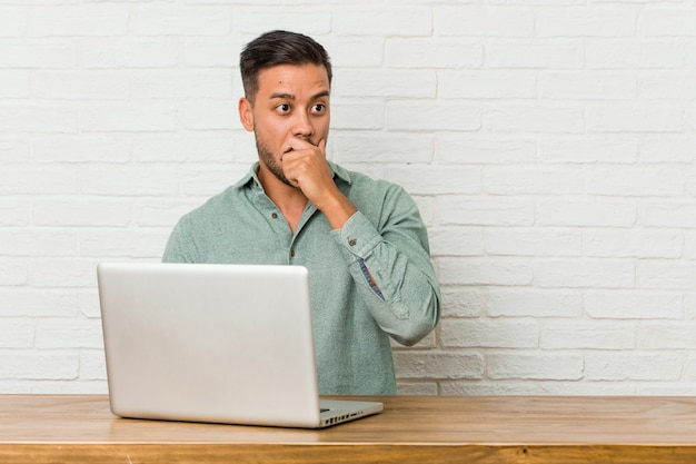 Young filipino man sitting working with his laptop shocked pointing with index fingers to a copy space.