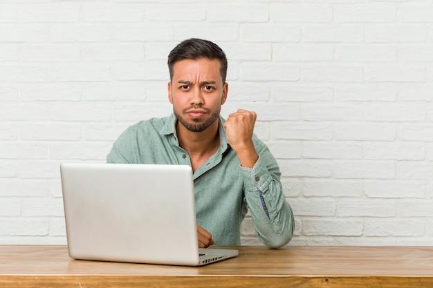 彼のラップトップで働いて座っている若いフィリピン人男性は、カメラに拳、攻撃的な表情を示しています。