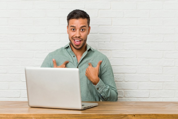 Young filipino man sitting working with his laptop surprised pointing with finger, smiling broadly.