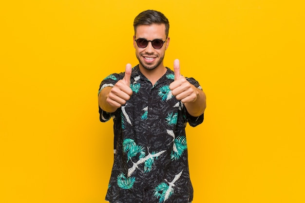 Young filipino man wearing summer clothes with thumbs ups, cheers about something, support and respect concept.
