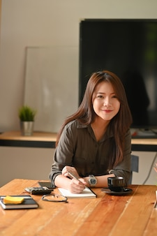 Young financial woman sitting on home office workplace and looking at camera.