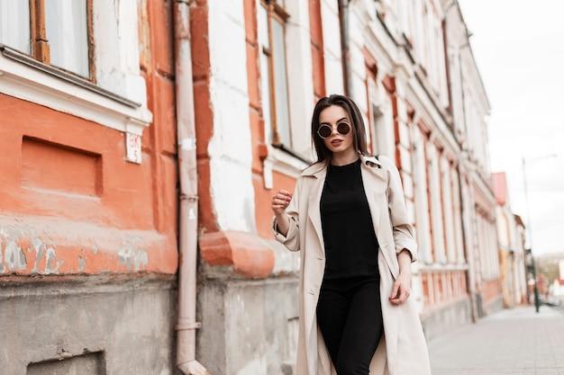 Молодая прекрасная красивая модель женщины в модных солнцезащитных очках в модном бежевом плаще гуляет возле старинного здания в городе. современная девушка наслаждается прогулкой по улице. весенняя модная одежда для женщин.
