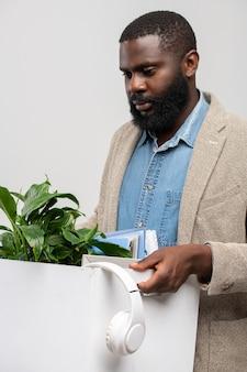 Молодой уволенный офис-менеджер африканского происхождения с грустью смотрит на коробку с наушниками, зелеными растениями и другими принадлежностями, покидая рабочее место