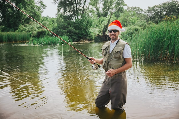 Young fisherman fishing on lake or river. 2021 new year or christmas time period. fisherman wears red holiday hat during fishing time.