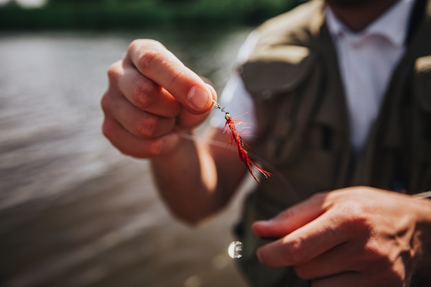 Young fisherman fishing on lake or river. close up and cut view of artificial plastic lure in guy's hands. fisherman adjusting his equipment before fishing process.