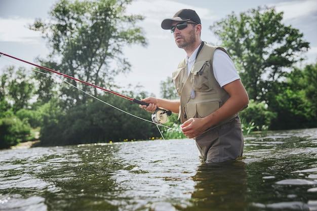 湖や川で釣りをする若い漁師。プロのロブや服を着たアクティブな男が水中に立ち、釣り竿を使って魚を捕まえようとしています。晴れた日のウォーターハンティング。