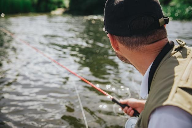 Молодой рыбак рыбалка на озере или реке. вид сзади парень держит в руке удочку и смотрит на воду. охота на озерную рыбу в летний солнечный день. человек один у воды.