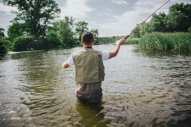 湖や川で釣りをする若い漁師。ロッドを持って釣り糸と一緒に使って、水中で美味しい魚を釣る男の背面図。川や湖に立ってください。