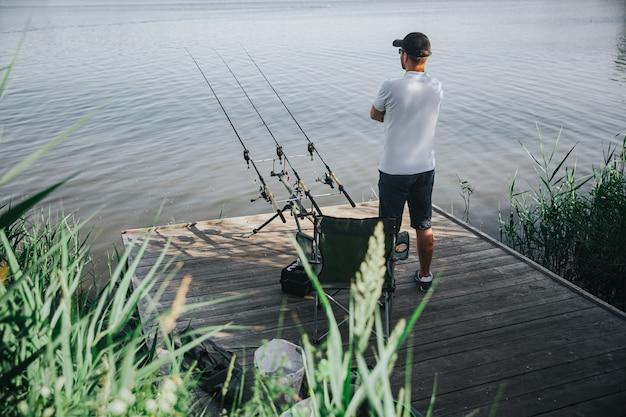 호수 또는 강에서 낚시하는 젊은 어 부. 남자의 모습의 뒷모습은 세 개의 낚싯대 옆에 강가에 서서 기대합니다. 물 udinr 화창한 아름다운 날을 찾고 있습니다. 신선한 생선을 기다리고 있습니다.