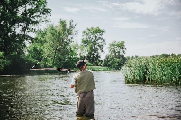 湖や川で釣りをする若い漁師。魚を捕まえようとしている川や湖の水の中の男のシルエットの背面図。釣り竿を使った狩猟。晴れた夏の日。