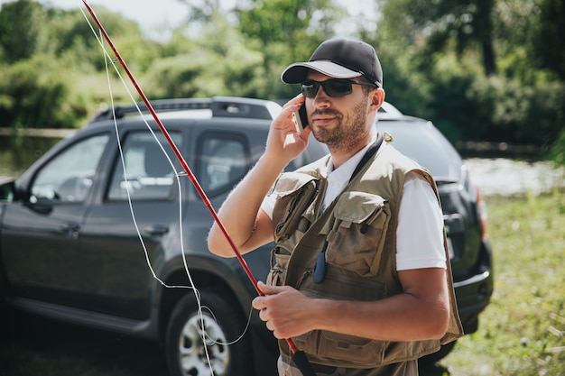 Молодой рыбак рыбалка на озере или реке. занят парень держит удочку и разговаривает по смартфону. стоять в одиночестве в машине во время переодевания.
