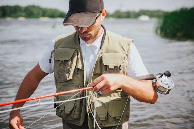 湖や川で釣りをする若い漁師。ロッドと釣り糸を手に持つ忙しい真面目な集中男。釣りの趣味の時間の準備。男は川や湖の水に立っています。