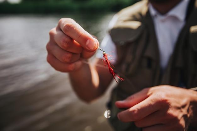 湖や川で釣りをする若い漁師。男の手の人工プラスチックルアーのクローズアップとカットビュー。漁師は釣りの前に自分の装備を調整します。