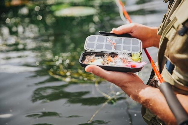 湖や川で釣りをする若い漁師。開いた箱で魚を捕まえるためにいくつかのプラスチック製の人工ルアーを持っている男の写真をクローズアップ。水中で一人で立ち、釣り竿を持ってください。