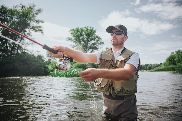 湖や川で釣りをする若い漁師。釣り糸を手にロッドを持って、魚を捕まえるために投げる集中男。水の川や湖の真ん中に立ってください。