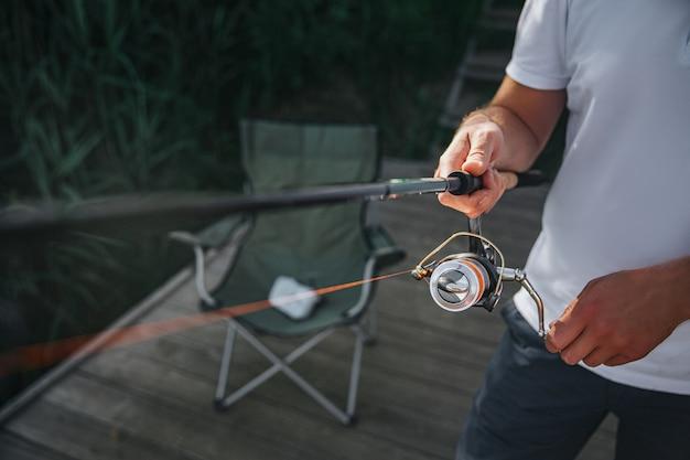 Молодой рыбак рыбалка на озере или реке. катушка и удилище в разрезе и крупным планом. парень использует рыболовное снаряжение для ловли рыбы или водной охоты. стоять один на пирсе.