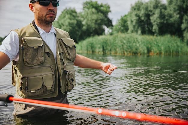 湖や川で釣りをする若い漁師。長い赤い棒を持って、湖や川の真ん中で一人で釣りをしている男のカットビュー。水に立つ。美しい晴れた日。