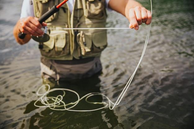湖や川で釣りをする若い漁師。水中に一人で立って、手に釣り糸を持っている男のカットビュー。釣りの時間のための機器の準備。